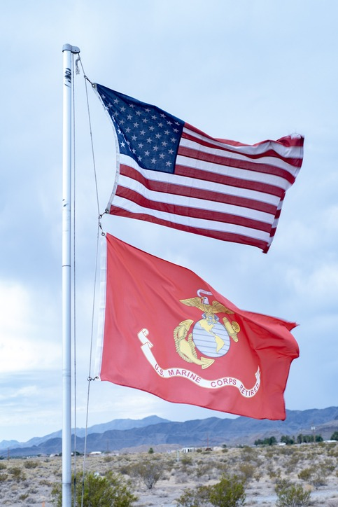 National flag of the United States of America and Marine Corp Retired red flag flying on flag pole