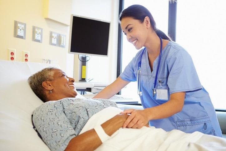 Happy Smiling Nurse Talking To Senior Woman In Hospital Room