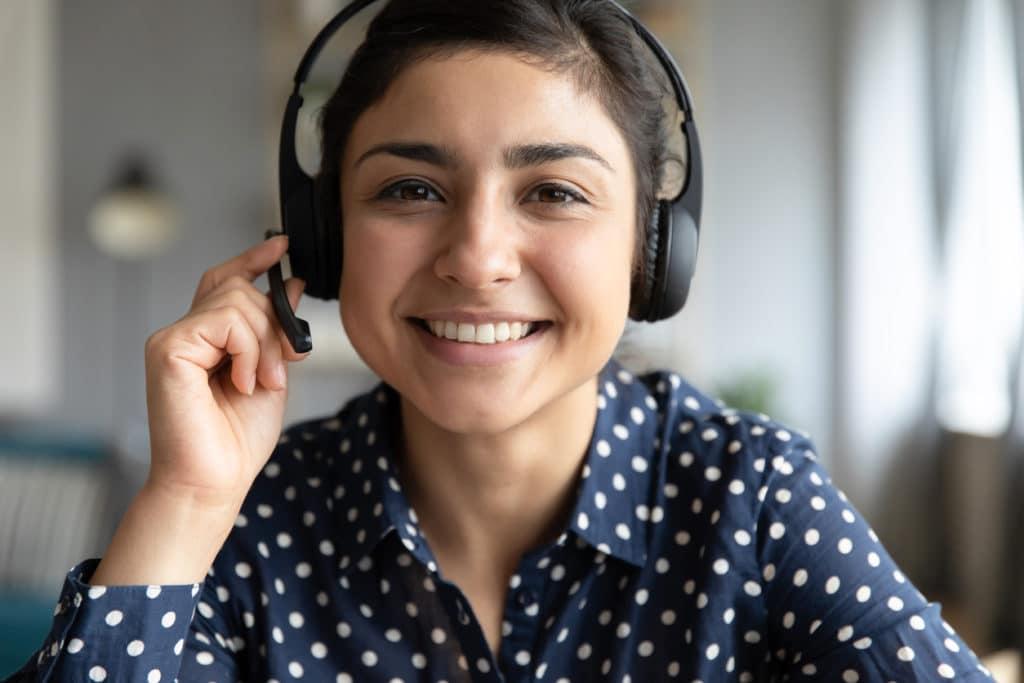 Smiling indian girl teacher counselor telesales agent wear wireless headset look at camera webcam, distance teaching, customer support service concept, telemarketing professional closeup portrait